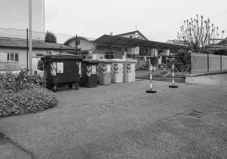 glass paper: TURIN, ITALY - CIRCA APRIL 2016: Reserved area for waste sorting bins for ecological reuse of materials such as glass paper cans with safety chain bollards in black and white Editorial