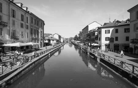 MILAN, ITALY - CIRCA APRIL 2016: Tourists on the bank of Naviglio Grande canal waterway in black and white