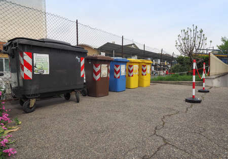 glass paper: TURIN, ITALY - CIRCA APRIL 2016: Reserved area for waste sorting bins for ecological reuse of materials such as glass paper cans with safety chain bollards