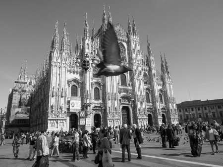 MILAN, ITALY - CIRCA APRIL 2016: Tourists queueing to visit Duomo di Milano (meaning Milan Cathedral) gothic church in black and white