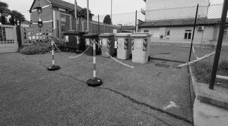 bollards: TURIN, ITALY - CIRCA APRIL 2016: Reserved area for waste sorting bins for ecological reuse of materials such as glass paper cans with safety chain bollards in black and white Editorial
