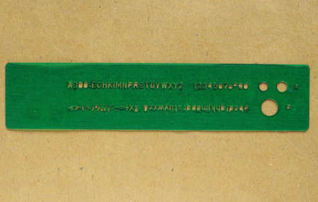 consists: A lettering guide template used to write uniform characters in a drawing nameplate. It consists of a sheet of green plastic with carved alphabet letters, numebers and other symbols