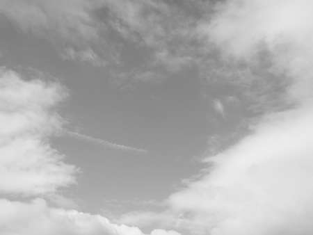 white clouds: Sky with clouds useful as a background in black and white
