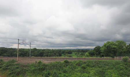 focus in foreground: English countryside seen from a train near Preston, with selective focus on the horizon and motion blur on the foreground