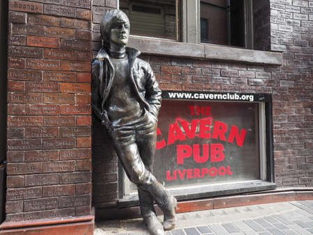 john lennon: LIVERPOOL, UK - CIRCA JUNE 2016: The Wall of Fame at the Cavern Pub opposite the Cavern Club where The Beatles played, with a statue of John Lennon Editorial
