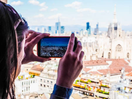 arial views: High dynamic range HDR Girl photographing arial view of the skyline of the city of Milan, Italy with a smartphone