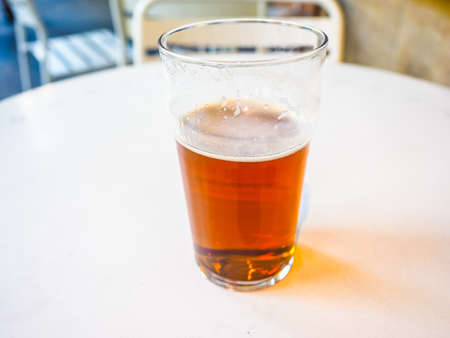 hdr background: High dynamic range (HDR) Pint of British ale on a pub table - selective focus on beer over blurred background Stock Photo