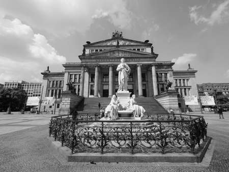 BERLIN, GERMANY - CIRCA JUNE 2016: Friedrich Schiller monument in front of Konzerthaus Berlin concert hall on the Gendarmenmarkt square in central Mitte district in black and white