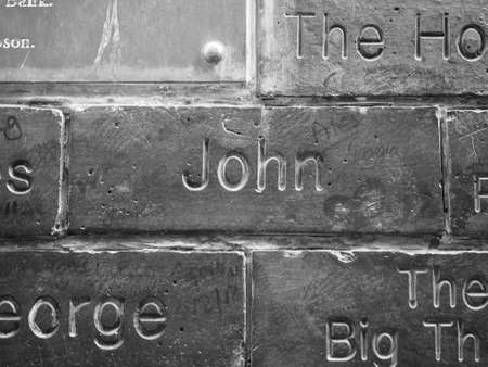 john lennon: LIVERPOOL, UK - CIRCA JUNE 2016: The Wall of Fame at the Cavern Pub opposite the Cavern Club where The Beatles played. Detail of John Lennon tile. in black and white Editorial