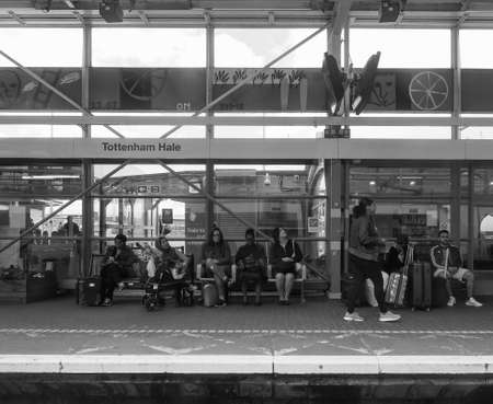 hale: LONDON, UK - CIRCA JUNE 2016: People waiting for transport at Tottenham Hale station platform in black and white Editorial