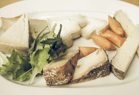 desaturated: Vintage desaturated Cheese platter with a selection of many fine handmade cheeses