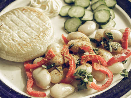 desaturated: Vintage desaturated Vegetarian main dish including cheese, mayonnaise, curry beans, peppers and cucumbers