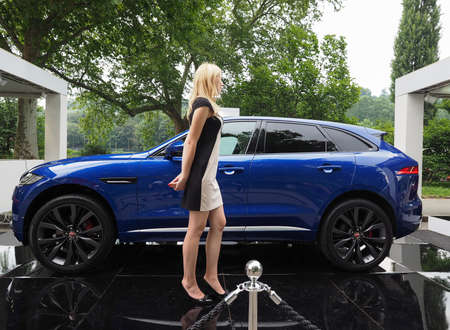 pace: TURIN, ITALY - CIRCA JUNE 2016: Model in front of the new Jaguar F Pace car in an outdoor car stand