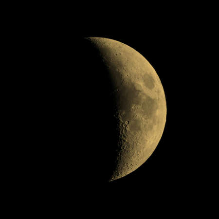 astrophoto: First quarter moon over dark black sky seen with a telescope from northern emisphere at night vintage sepia