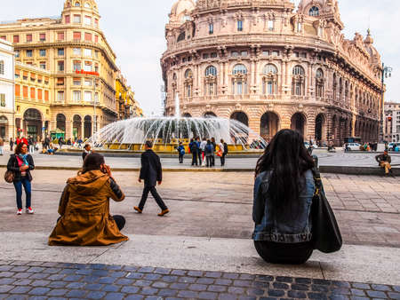 16: GENOA, ITALY - MARCH 16, 2014: Tourists visiting Piazza De Ferrari main square and fountain (HDR)