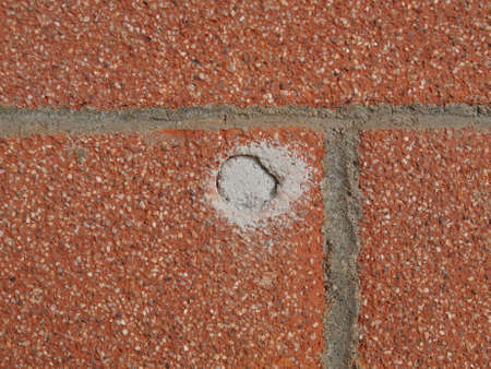 clavados: pared de ladrillo rojo con un agujero fijo Foto de archivo