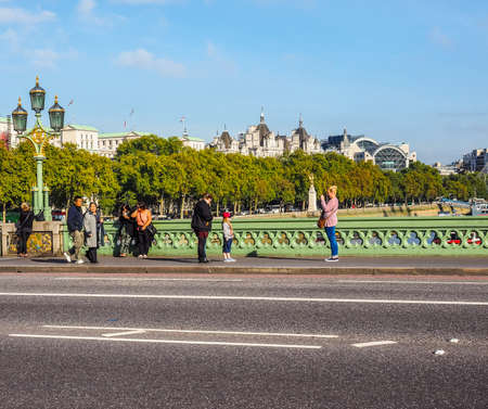 westminster bridge: LONDON, UK - SEPTEMBER 28, 2015: Tourists crossing Westminster Bridge over River Thames (HDR)