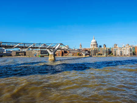 millennium bridge: LONDON, UK - SEPTEMBER 28, 2015: People crossing the Millennium Bridge over River Thames linking the City of London with the South Bank between St Paul Cathedral and Tate Modern art gallery (HDR) Editorial