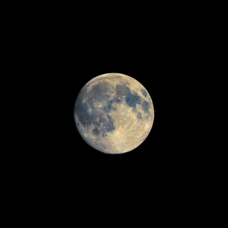 astrophoto: Full moon seen with an astronomical telescope, with enhanced colours to show the real colours of terrain surface - with copy space Stock Photo