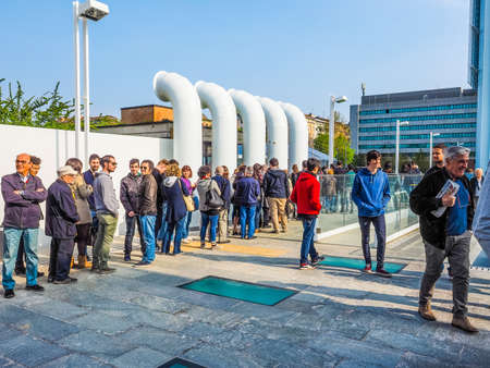 queueing: TURIN, ITALY - APRIL 11, 2015: People queueing to visit the new Intesa San Paolo skyscraper designed by Renzo Piano Building Workshop which just opened today and is the highest building in Turin (HDR)