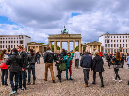 linking: BERLIN, GERMANY - MAY 10, 2014: Tourists visiting the Brandenburger Tor (Brandenburg Gate) linking East and West Berlin (HDR)