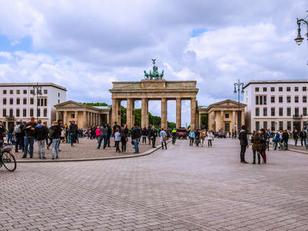 west germany: BERLIN, GERMANY - MAY 10, 2014: Tourists visiting the Brandenburger Tor (Brandenburg Gate) linking East and West Berlin (HDR)