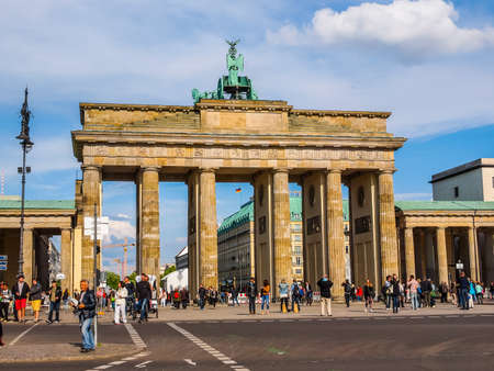 linking: BERLIN, GERMANY - MAY 09, 2014: Tourists visiting the Brandenburger Tor (Brandenburg Gate) linking East and West Berlin (HDR)