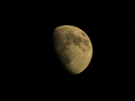 seen: Gibbous moon over dark black sky with stars seen with a telescope from northern emisphere at night vintage sepia