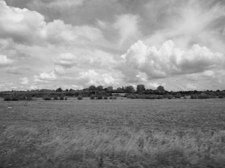 rural skyline: English countryside seen from a train to London, with selective focus on the horizon and motion blur on the foreground in black and white