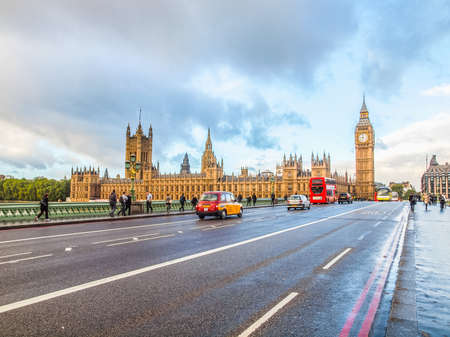 LONDON, ENGLAND, UK - OCTOBER 23: People crossing the world famous Westminster Bridge in front of the Houses of Parliament on October 23, 2013 in London, England, UK (HDR) Editorial