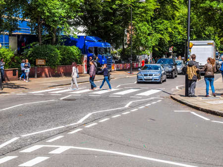 album cover: LONDON, ENGLAND, UK - JUNE 18: People crossing the Abbey Road zebra crossing made famous by the 1969 Beatles album cover on June 18, 2011 in London, England, UK (HDR) Editorial