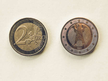 geld: Vintage looking Two Euro coins currency of the European union common side and German side Stock Photo