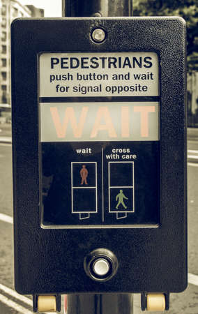 wait sign: Vintage looking A pedestrian crossing sign - press button and wait for signal opposite