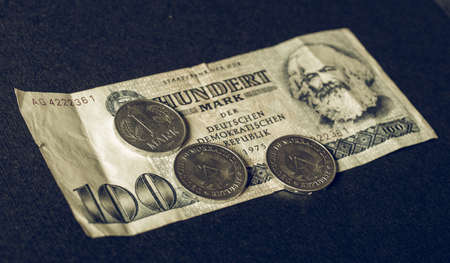 karl: 100 Mark banknote from the DDR (East Germany) with Karl Marx with 1 Mark coin - Note: Vintage looking no more in use since german reunification in 1989