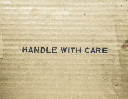 handle with care: Vintage looking Handle with care tag on a corrugated cardboard packet