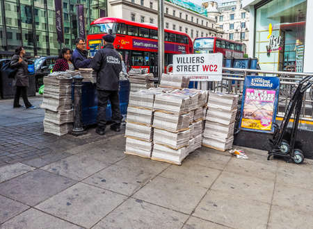 evening newspaper: LONDON, UK - JUNE 09, 2015: Distribution of the Evening Standard free newspaper on the Strand near Charing Cross station (HDR)