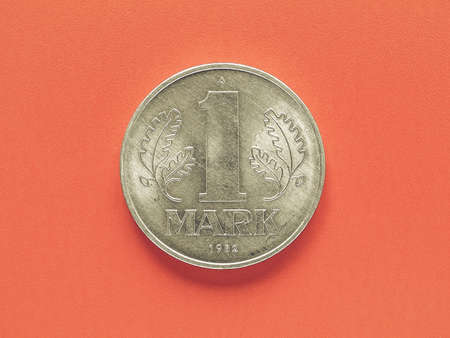 east germany: Vintage looking One Mark coin from the DDR (East Germany) over red background