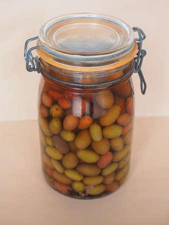 brine: Olives (Olea europaea sylvestris) vegetables vegetarian food in brine in a glass jar
