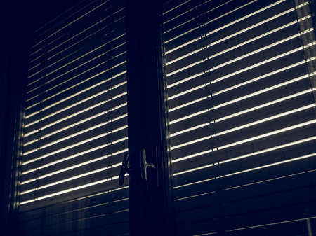 seen: Vintage looking Silhouette of windows blinds seen from a dark room against the sun light Stock Photo