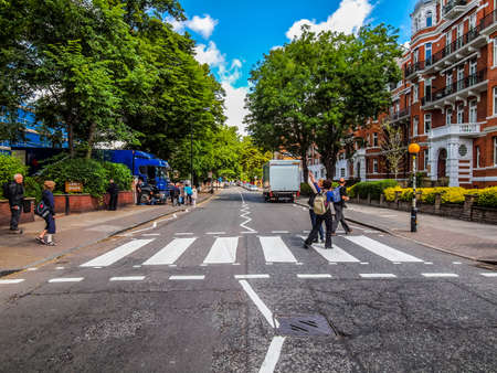 the beatles: LONDON, ENGLAND, UK - JUNE 18: People crossing the Abbey Road zebra crossing made famous by the 1969 Beatles album cover on June 18, 2011 in London, England, UK (HDR) Editorial