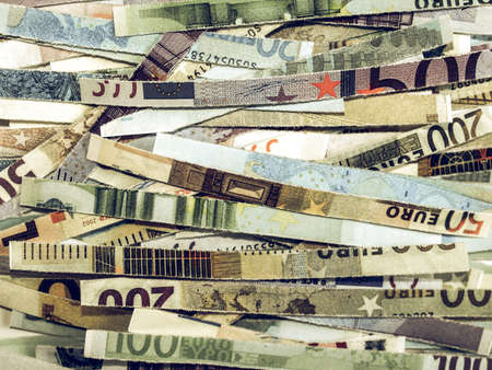 money to burn: Vintage looking Money to burn - banknotes cut with a paper shredder Stock Photo