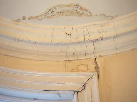 Damage caused by damp and moisture on a wall and ceiling