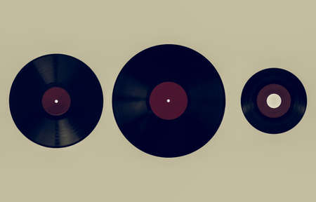 shellac: Vintage looking Size comparison of many analogue recording media for music. Left to right: shellac record 78 rpm, vinyl record 33 rpm and 45 rpm - red label Stock Photo