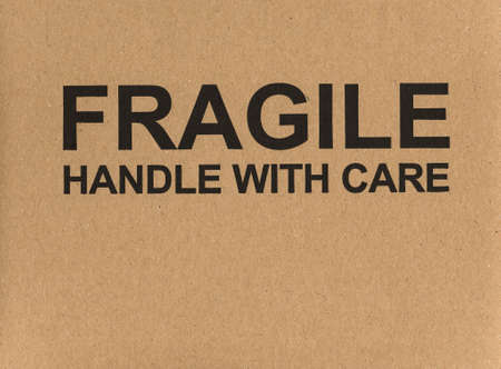 handle with care: Fragile handle with care warning sign label tag on a cardboard box