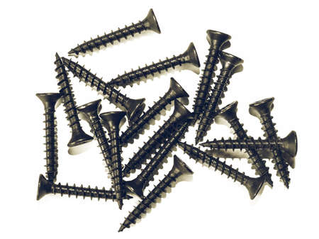 metal fastener: Vintage looking A group of many screws used as fasteners over white background
