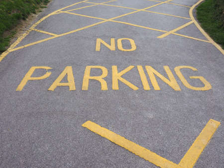 no parking sign: No parking sign written on yellow on the street tarmac Stock Photo