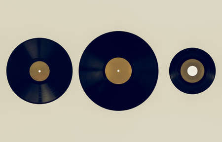 shellac: Vintage looking Size comparison of many analogue recording media for music. Left to right: shellac record 78 rpm, vinyl record 33 rpm and 45 rpm - yellow label
