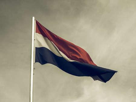 nederland: Vintage looking Flag of Netherlands over a blue sky Stock Photo