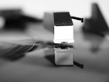 Vinyl record spinning on a turntable, focus on needle - in black and white Stock Photo