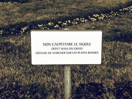multilingual: Vintage looking Multilingual dont walk on the grass sign